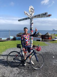 man-with-bicycle-points-to-lands-end-sign-on-his-charity-cycle-for-the-david-nott-foundation